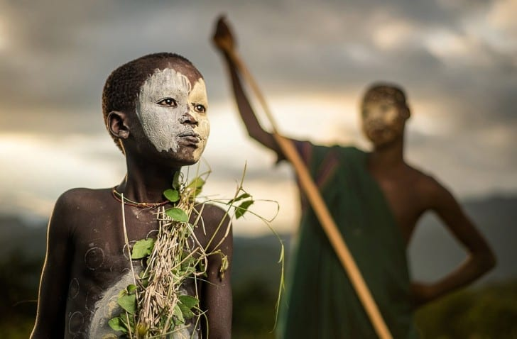 A boy of the nomadic Suri tribe of Ethiopia, in traditional body paint and attire